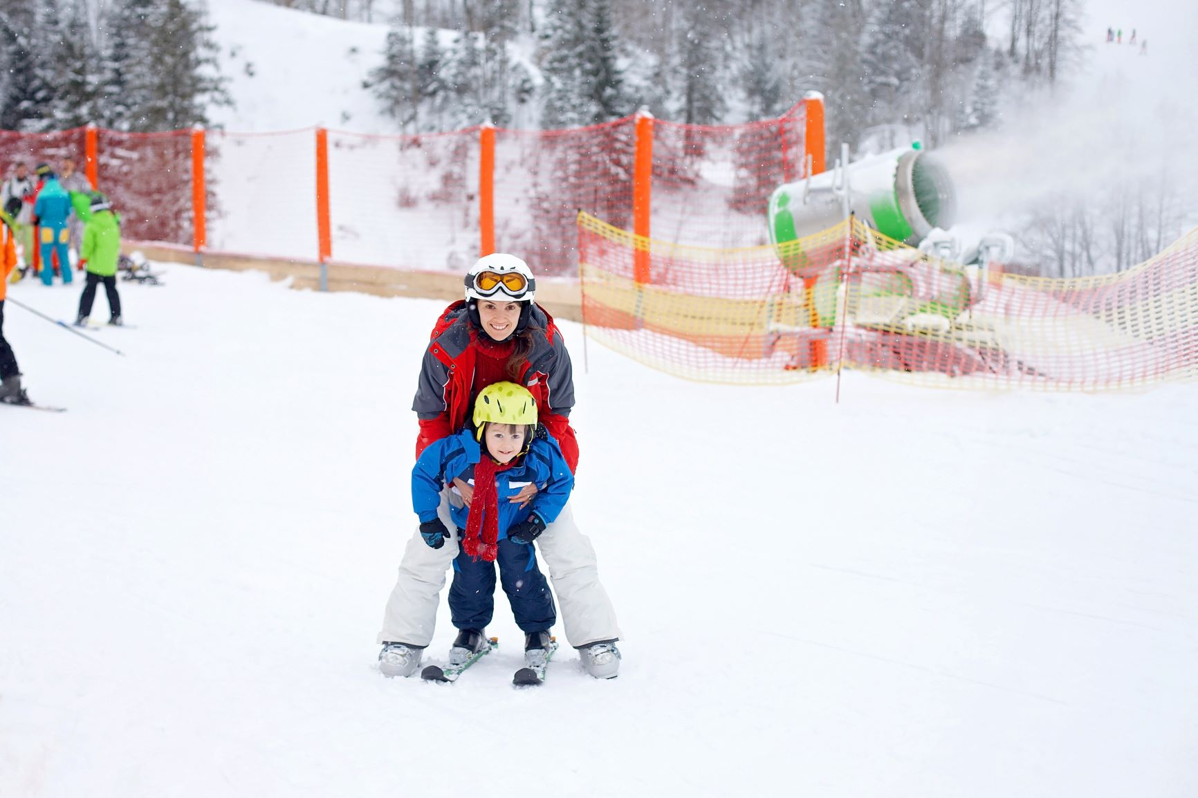 Canva - Beautiful young mom and her toddler boy, skiing in mountains