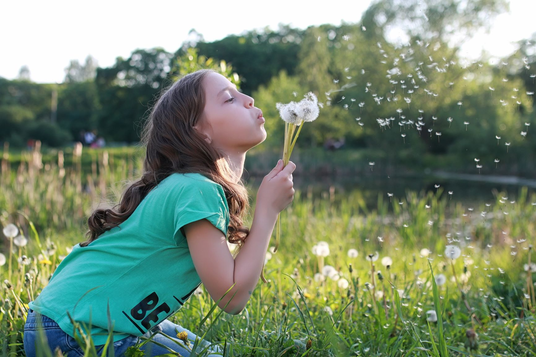 3. Canva - Teen blowing seeds from a dandelion flower in a spring park