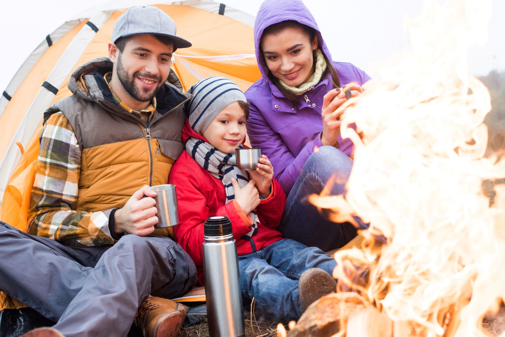 Canva - Family drinking tea near burning fire